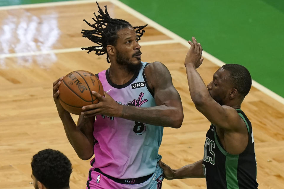 Miami Heat's Trevor Ariza, left, looks for an opening as Boston Celtics' Kemba Walker (8) tries to block in the first half of a basketball game, Sunday, May 9, 2021, in Boston. (AP Photo/Steven Senne)