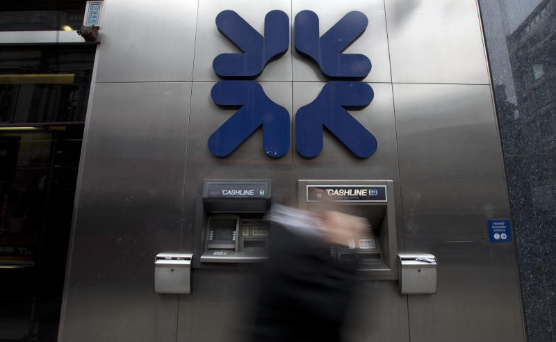 A pedestrian walks past the logo of the Royal Bank Of Scotland (RBS), and a cash dispenser as the bank announced its results for 2012 in London, Thursday, Feb. 28, 2013. Part-nationalized RBS said Thursday it ended 2012 with massive losses after it set aside more cash to compensate customers who were mis-sold financial products and to pay fines related to a rate-rigging scandal. The bank, which is 82 percent owned by British taxpayers, said its fourth quarter losses increased 44 percent from a year earlier, to 2.60 billion pounds. That led to a full-year loss of 5.97 billion pounds ($9 billion), up from a shortfall of 2 billion pounds in 2011.(AP Photo/Alastair Grant)