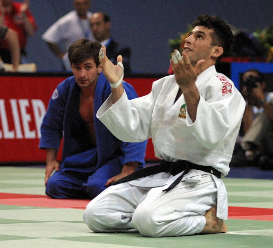 Munich, GERMANY:  (FILES) Iranian Arash Miresmaeili (R) thanks God 28 July 2001 in Munich after defeating Ukrainian Musa Nastuyev in the men's -66 kg category at the world judo championships. The two-time world champion was disqualified from competiting in the under 66 kg at the Olympic Games in Athens, 15 August 2004 after weighing in over the his category, according to the International Judo Federation.        AFP PHOTO JACQUES DEMARTHON  (Photo credit should read JACQUES DEMARTHON/AFP via Getty Images)
