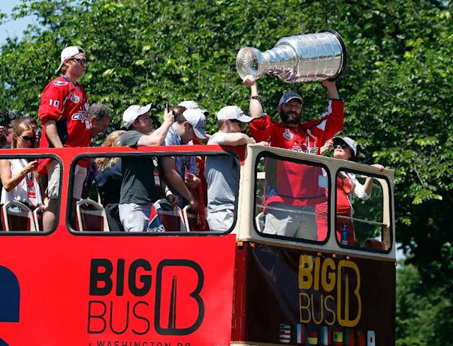 Washington Capitals captain Alex Ovechkin holds up the Stanley Cup during the team's victory parade (AFP Photo/Alex Brandon)