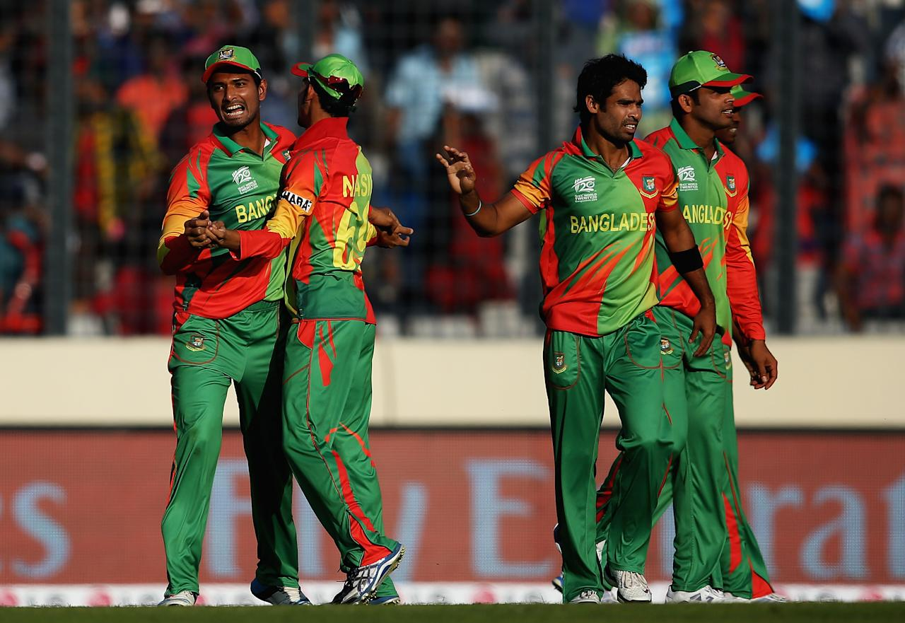 DHAKA, BANGLADESH - MARCH 16:  Mahmudullah  (L) of Bangladesh is congartuated by team mates after catching Dawlat Zadran  of Afghanistan during the ICC World Twenty20 Bangladesh 2014 match between Bangladesh and Afghanistan at the Sher-e-Bangla Mirpur Stadium on March 16, 2014 in Dhaka, Bangladesh.  (Photo by Matthew Lewis-IDI/IDI via Getty Images)