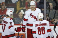Carolina Hurricanes' Dougie Hamilton, center, celebrates his goal against the Calgary Flames with teammates during second-period NHL hockey game action in Calgary, Alberta, Saturday, Dec. 14, 2019. (Jeff McIntosh/The Canadian Press via AP)