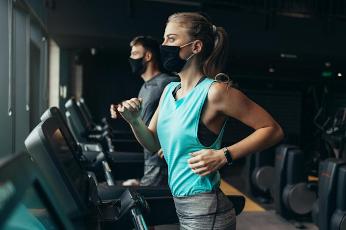 Young fit woman and man running on treadmill in modern fitness gym. They keeping distance and wearing protective face masks. Coronavirus world pandemic and sport theme.
