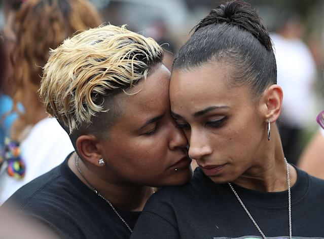 <p>Angel Ayala (L) and Carla Montanez hug as they mourn the loss of their best friend in the mass shooting at the Pulse gay nightclub as people gather together outside the club during a one-year anniversary memorial service on June 12, 2017 in Orlando, Florida. (Joe Raedle/Getty Images) </p>