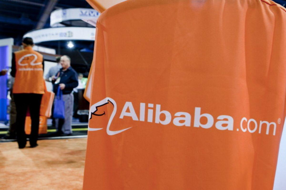 The Alibaba.com Ltd. logo is seen at the company's booth during the 2012 International Consumer Electronics Show (CES) in Las Vegas, Nevada, U.S., on Friday, Jan. 13, 2012. Alibaba Group Holding Ltd. is considering reducing the size of a loan for a potential Yahoo! Inc. acquisition to around $3 billion from the original target of $4 billion in order to use its cash instead. Photographer: Andrew Harrer/Bloomberg via Getty Images