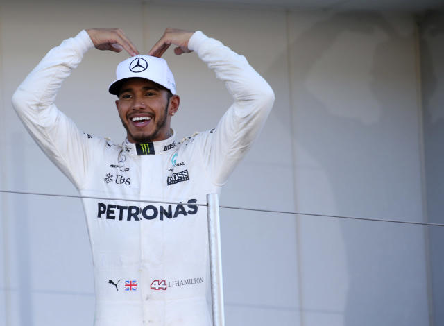 <p>Mercedes driver Lewis Hamilton of Britain poses on the podium for his team crew after winning the Japanese Formula One Grand Prix at Suzuka Circuit in Suzuka, central Japan, Sunday, Oct. 8, 2017. (AP Photo/Toru Takahashi)</p>