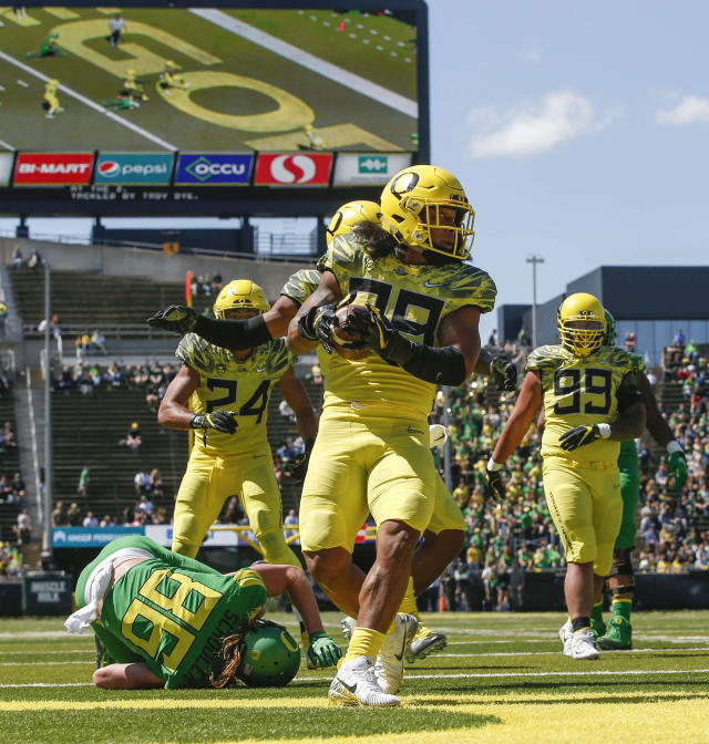 Oregon linebacker Kaulan Apelu, center, intercepts a Justin Herbert pass and turns to start a run for a touchdown during the Oregon spring college football game Saturday, April 21, 2018, in Eugene, Ore. (Andy Nelson/The Register-Guard via AP)