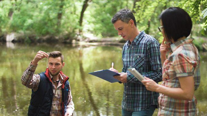Three ecologists wearing casual clothing exploring lake and taking water sample.