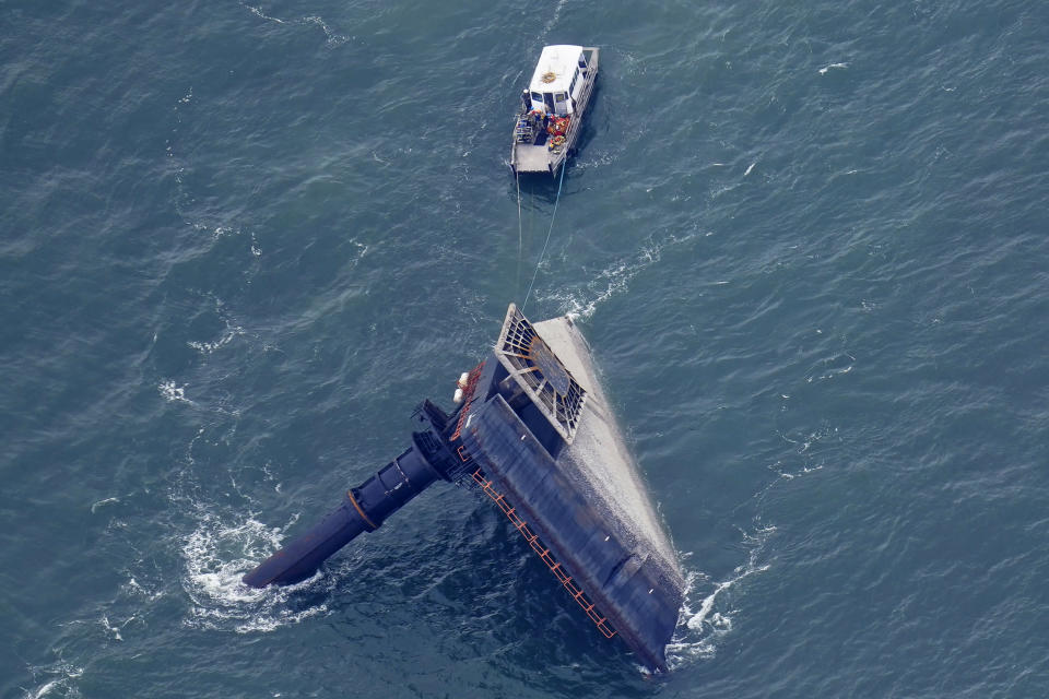 A rescue boat is seen next to the capsized lift boat Seacor Power seven miles off the coast of Louisiana in the Gulf of Mexico Sunday, April 18, 2021. The vessel capsized during a storm on Tuesday. (AP Photo/Gerald Herbert)