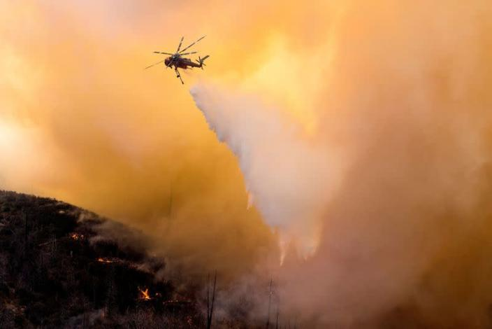 FILE PHOTO: A helicopter makes a water drop over a wildfire in the Angeles National Forest during the Bobcat Fire in Los Angeles