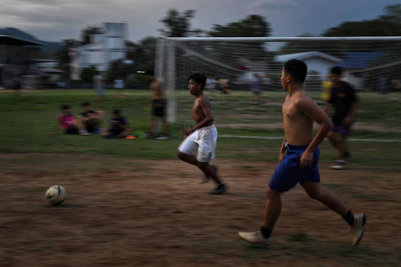 "This photo taken on June 14, 2019 shows Wild Boars footballer Ekarat Bew Wongsukchan (C) taking part in a training session at the the football academy of Ekkapol Coach Ek Chantawong, who were both trapped with 11 others from the ""Wild Boars"" team in the Tham Luang cave last year, in the Mae Sai district of Chiang Rai province. - When they entered the cave most of the ""Wild Boars"" were poor, some were stateless and all were unknown. They emerged 18 days later from its flooded chambers at the centre of a global media storm - courted by producers, authors and talk show hosts eager to retell their remarkable survival tale. (Photo by Lillian SUWANRUMPHA / AFP) / TO GO WITH Thailand-accident-cave-rescue, FOCUS by Sippachai KUNNUWONG and Sophie DEVILLER (Photo credit should read LILLIAN SUWANRUMPHA/AFP/Getty Images)"