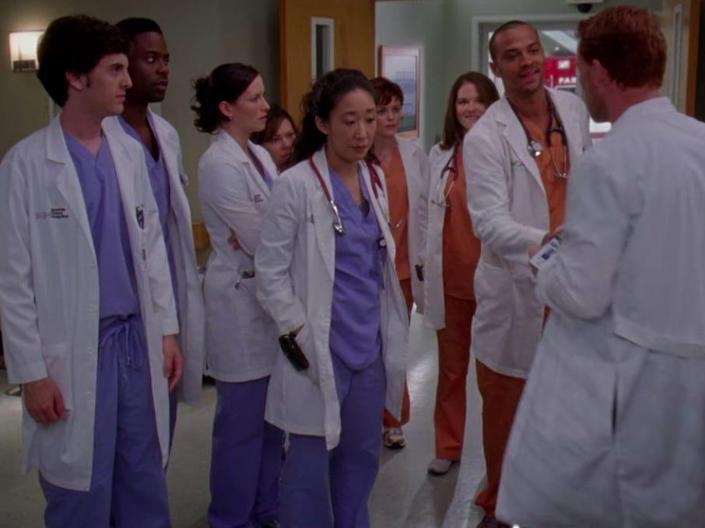 The cast of greys anatomy standing in the lobby wearing scrubs and white coats
