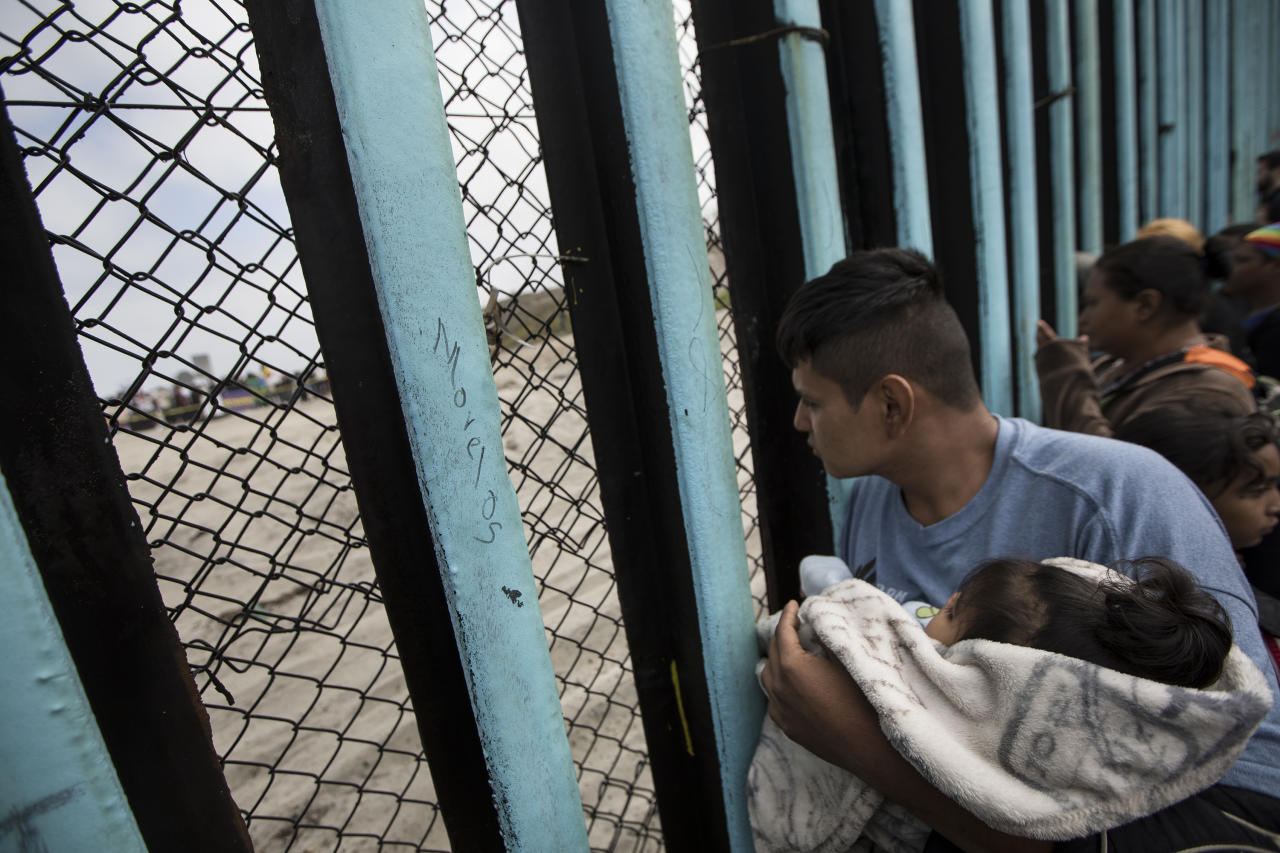<p>A member of the Central American migrant caravan, holding a child, looks through the border wall toward a group of people gathered on the U.S. side, as he stands on the beach where the border wall ends in the ocean, in Tijuana, Mexico, April 29, 2018. (Photo: Hans-Maximo Musielik/AP) </p>