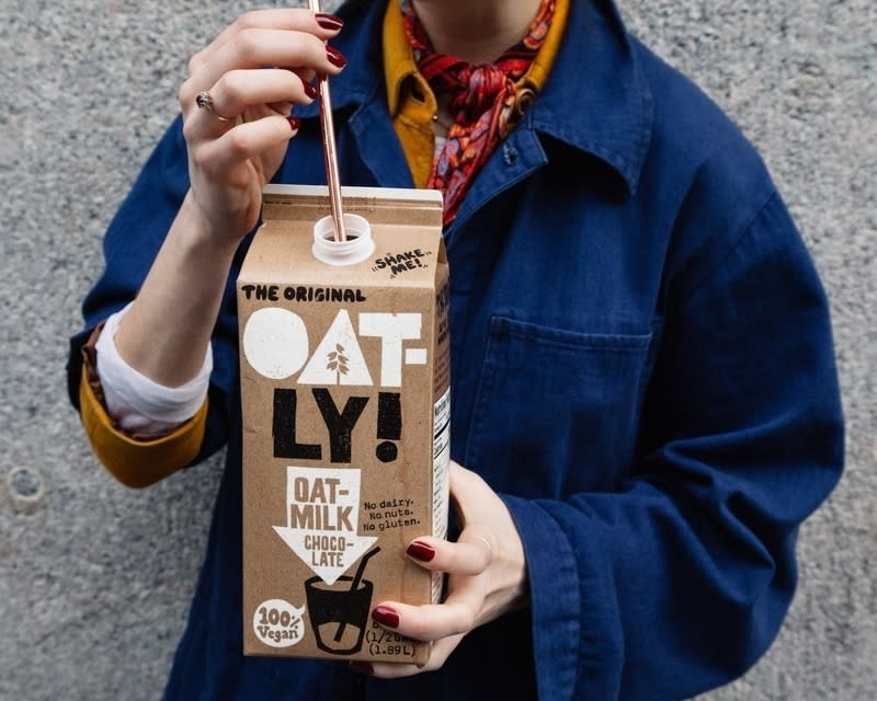 A person drinking oatly out of a straw