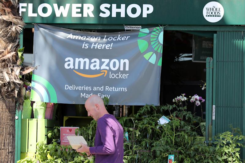A man walks past an advert for Amazon Locker outside a Whole Foods Market store in Santa Monica, California, U.S. March 19, 2018. REUTERS/Lucy Nicholson