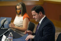 Arizona Secretary of State Katie Hobbs, left, and Arizona Gov. Doug Ducey sign election documents to certify the election results for federal, statewide, and legislative offices and statewide ballot measures at the official canvass at the Arizona Capitol Monday, Nov. 30, 2020, in Phoenix. (AP Photo/Ross D. Franklin, Pool)