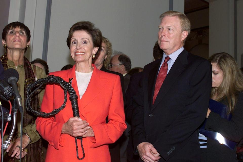 <p>After being elected House Whip in October 2001, Pelosi poses for a very on-theme photo holding an actual whip. </p>