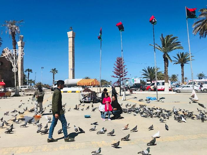 Libyans walk in the Tripoli's Martyr Square as fresh fighting flared south of the capital (AFP Photo/Mahmud TURKIA)