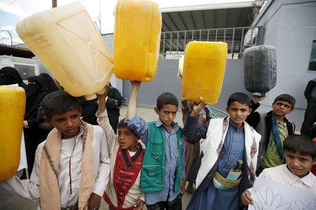 Boys hold up jerrycans to represent drinking water during a protest against a Saudi blockade of Yemen's ports, outside the United Nations' offices in Sanaa, Yemen October 19, 2015. REUTERS/Khaled Abdullah