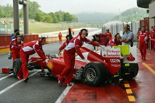 Ferrari F1 team members help Fernando Alonso into the pits of the Mugello track