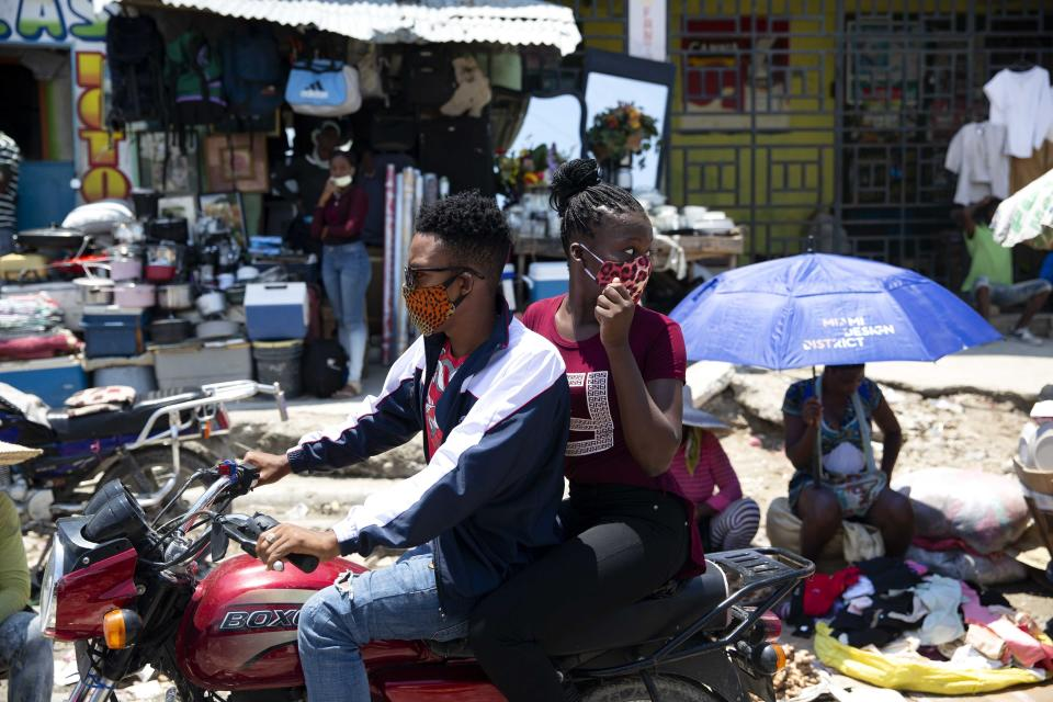 FILE - In this April 15, 2020 file photo, people ride on a motorcycle as they wear face masks to protect themselves from the spread of the new coronavirus in Port-au-Prince, Haiti. (AP Photo/Dieu Nalio Chery)
