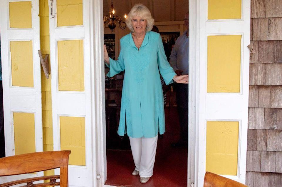 """<p>While visiting St. Kitts and Nevis on a <a href=""""https://www.townandcountrymag.com/society/tradition/g26850147/prince-charles-camilla-parker-bowles-royal-tour-caribbean-2019-photos/"""" rel=""""nofollow noopener"""" target=""""_blank"""" data-ylk=""""slk:royal tour of the Caribbean"""" class=""""link rapid-noclick-resp"""">royal tour of the Caribbean</a>, Camilla wore a tiffany blue, embroidered caftan with white pants, turquoise drop earrings, and gold ballet flats. </p>"""