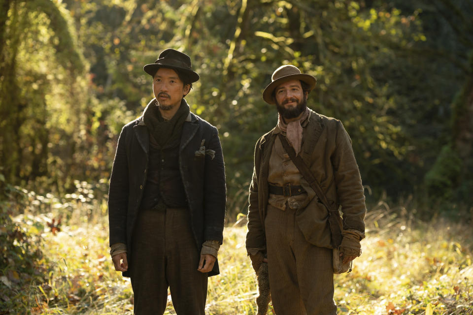 """This image released by A24 Films shows Orion Lee, left, and John Magaro in a scene from """"First Cow."""" (Allyson Riggs/A24 Films via AP)"""