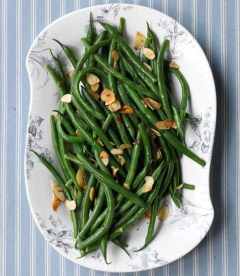 """<p>Lighten up a heavy holiday meal with this verdant side dish of green beans tossed in almond-garlic oil. If you want to kick up the flavor even more, add one Tbsp of vinegar just before serving.</p><p><a href=""""https://www.womansday.com/food-recipes/food-drinks/recipes/a11345/green-beans-toasted-garlic-almonds-recipe-124683/"""" rel=""""nofollow noopener"""" target=""""_blank"""" data-ylk=""""slk:Get the Green Beans with Toasted Garlic and Almonds recipe."""" class=""""link rapid-noclick-resp""""><em><strong>Get the Green Beans with Toasted Garlic and Almonds recipe.</strong></em></a></p>"""