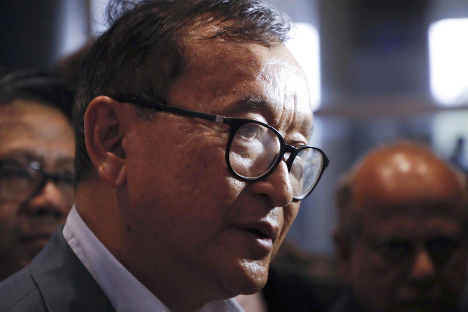 FILE - In this Nov. 9, 2019, file photo, Cambodia's exiled opposition leader Sam Rainsy talks with the media upon arrival at Kuala Lumpur International Airport in Sepang, Malaysia, in a bid to return to his homeland after Thailand had earlier blocked him from entering. Phnom Penh Municipal Court has convicted and sentenced the exiled leader and senior members of the country's banned opposition party to more than 20 years in prison, effectively barring them from ever returning home. The decision taken by the court late Monday, March 1, 2021 was condemned by the head of the Cambodia National Rescue Party , or CNRP, human rights organizations and the United States embassy. The trial was held in absentia as all the party leaders are living abroad. (AP Photo/Vincent Thian, File)