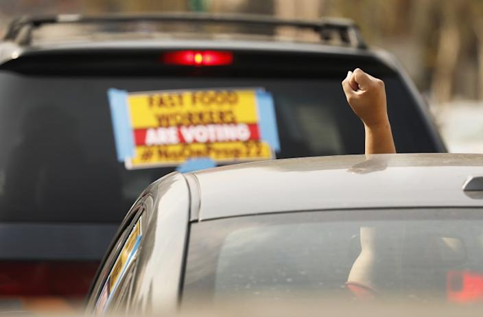 LOS ANGELES, CA - OCTOBER 08: Rideshare driver M.J. raises her fist in support as app based gig workers held a driving demonstration with 60-70 vehicles blocking Spring Street in front of Los Angeles City Hall urging voters to vote no on Proposition 22, a November ballot measure that would classify app-based drivers as independent contractors and not employees or agents, providing them with an exemption from California's AB 5. The action is part of a call for stronger workers' rights organized by the Mobile Workers Alliance with 19,000 drivers in Southern California and over 40,000 in all of California. Los Angeles on Thursday, Oct. 8, 2020 in Los Angeles, CA. (Al Seib / Los Angeles Times