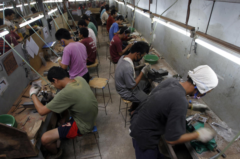 FILE PHOTO: Former illegal gunsmiths work at the gun assembly line of Shooters Arms, a gun manufacturing company in Cebu City exporting different kinds of weapons to other countries, July 7, 2012. (Source: REUTERS/Erik De Castro)