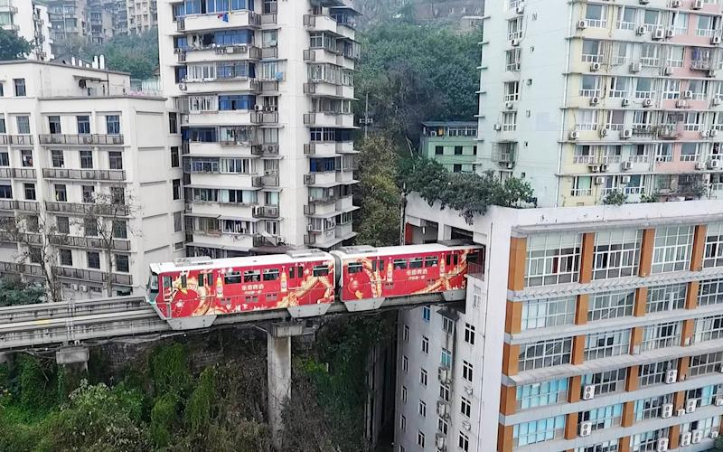 Next stop, your living room! A train passes through a residential building in Chongqing, China - 2017 VCG