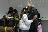 Members of the Mogul family, a father kisses his daughter, who arrived on a flight from Charlotte, North Carolina, in the U.S., at Terminal 5 of Heathrow Airport in London, Monday, Aug. 2, 2021. Travelers fully vaccinated against coronavirus from the United States and much of Europe were able to enter Britain without quarantining starting today, a move welcomed by Britain's ailing travel industry. (AP Photo/Matt Dunham)