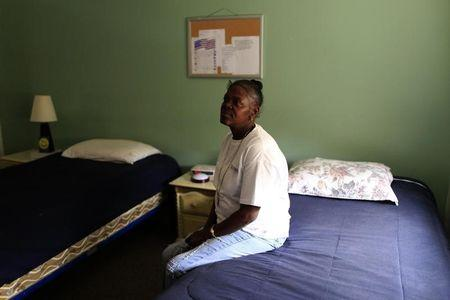 Army veteran Cassandra Lewis, 52, sits on her bed at New Directions women's house