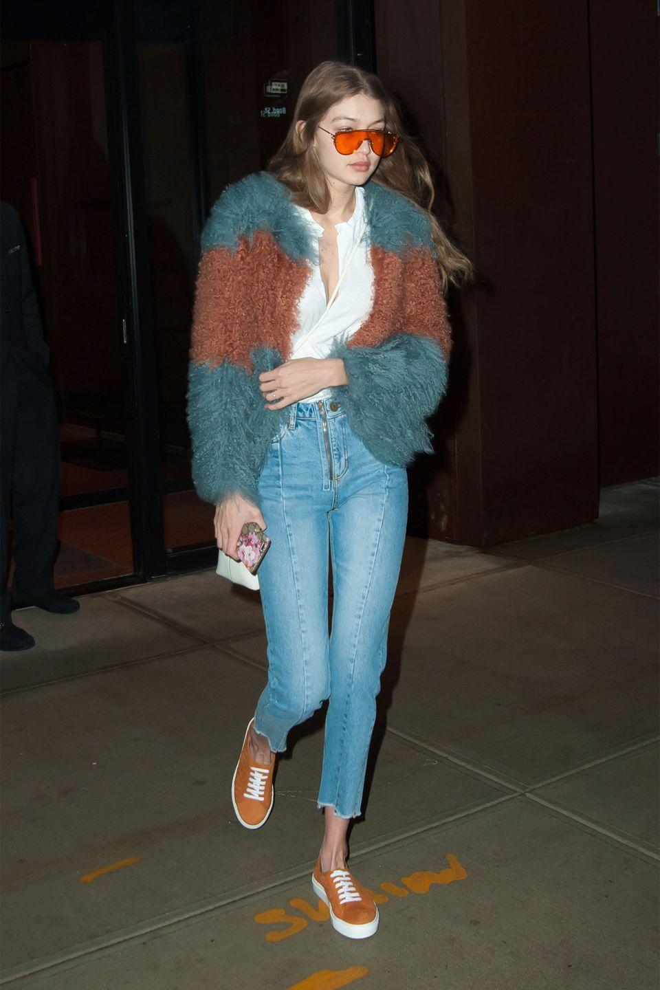 <p>In teal and auburn shag coat, white t-shirt, Sandro cropped jeans, suede sneakers by M. Gemi, a Gucci phone case and Gentle Monster orange tinted sunglasses while leaving her apartment in NYC.</p>