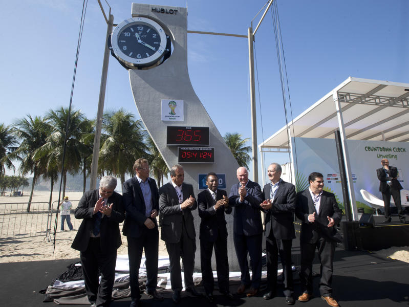 FIFA Secretary General Jerome Valcke, second left, Vice Governor of Rio de Janeiro Luiz Fernando Pezao, third left, Brazilian football icon Pele, center, Hublot Chairman Jean-Claude Biver, third right, and Minister of Sports Aldo Rebelo, second right, attend the unveiling of the Hublot Countdown Clock designed by the late architect Oscar Niemeyer; an event marking one year to the kick-off of the 2014 FIFA World Cup, at the Copacabana beach in Rio de Janeiro, Brazil, Wednesday, June 12, 2013. (AP Photo/Silvia Izquierdo)