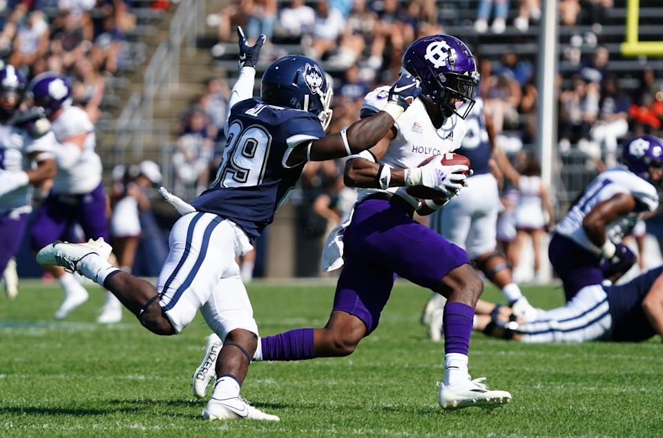 Holy Cross defensive back John Smith intercepts a pass intended for Connecticut wide receiver Jahkai Gill.