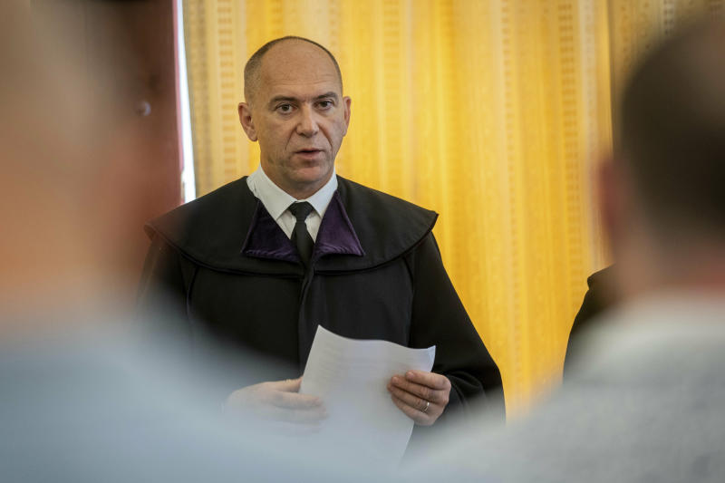 Judge Erik Mezolaki announces the second verdict in the migrant smuggling case known as the Parndorf-case in the Court of Appeal of Szeged in Szeged, southern Hungary, Thursday, June 20, 2019.  Hungarian court has extended the prison sentences of four human traffickers convicted last year for their roles in a 2015 in which 71 migrants suffocated to death in the back of a refrigerated truck found on a highway in Austria. (Tibor Rosta/MTI via AP)