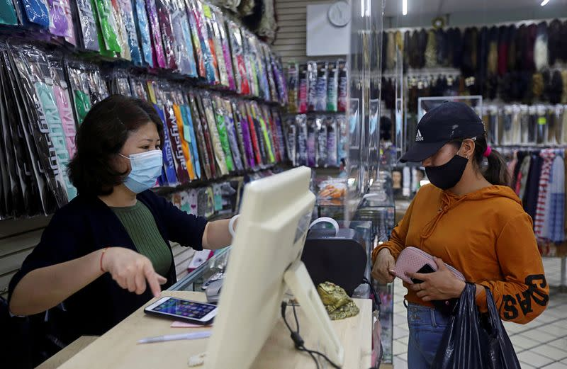 Pan Emi, wife of Gan Xianbing, interacts with a client at her store in Guadalajara
