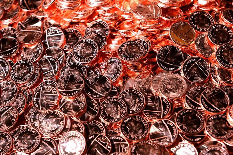 Shiny new pennies come off the production line at the Royal Mint in Pontyclun, Wales (PA)
