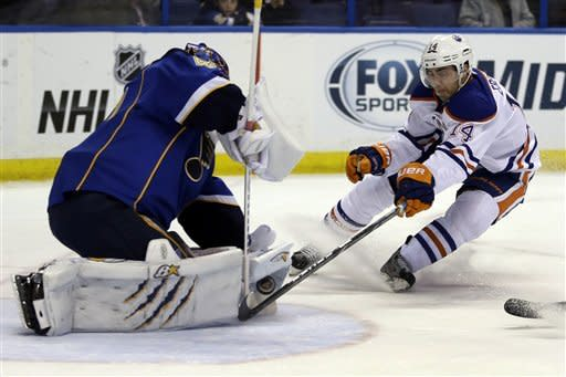 Edmonton Oilers' Jordan Eberle, right, reaches for the puck as it is stopped by St. Louis Blues goalie Jaroslav Halak, of Slovakia, during the first period of an NHL hockey game Friday, March 1, 2013, in St. Louis. (AP Photo/Jeff Roberson)