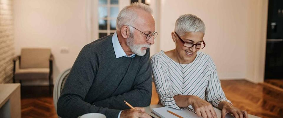 A happy senior couple calculating their finances in a beautiful home.