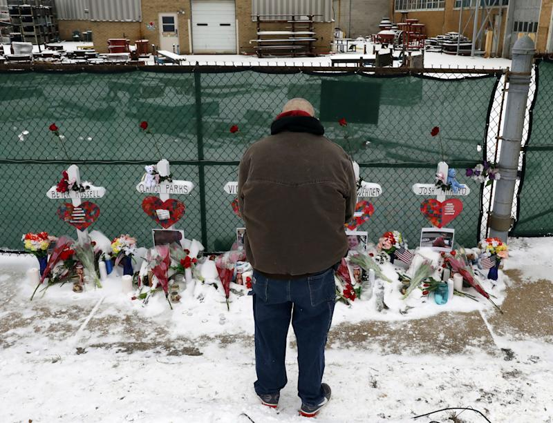 A man prays at a makeshift memorial, Feb. 17, 2019, in Aurora, Ill., near Henry Pratt Co. manufacturing company where several were killed on Friday.