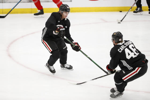 Chicago Blackhawks right wing Patrick Kane, left, looks to pass the puck against defender Lucas Carlsson, right, during NHL hockey practice at Fifth Third Arena on Monday, July 13, 2020, in Chicago. (AP Photo/Kamil Krzaczynski)