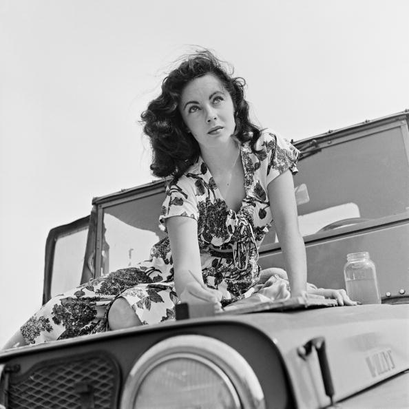 <p>Elizabeth enjoyed painting, especially at a young age. Here, the actress is seen painting outside in the summer of 1947 on the hood of a car.</p>