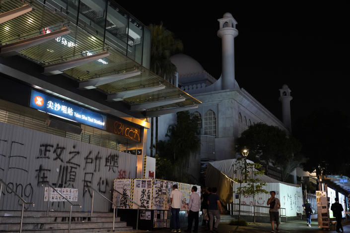 People walk past a mosque next to a subway station at a main road in Hong Kong Sunday, Oct. 20, 2019, Hong Kong. A water cannon truck and armored car led a column of dozens of police vans up and down Nathan Road, a major artery lined with shops, to spray a stinging blue-dyed liquid as police moved to clear the road of protesters and barricades.(AP Photo/Vincent Yu)