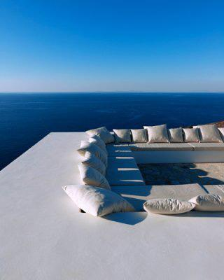 A getaway on the Greek island of Antiparos features a contemporary roof deck overlooking the Mediterranean. The wrap-around banquette is furnished with pillows and cushions that blend in with the surrounding architecture. (Photo: Mads Mogensen)