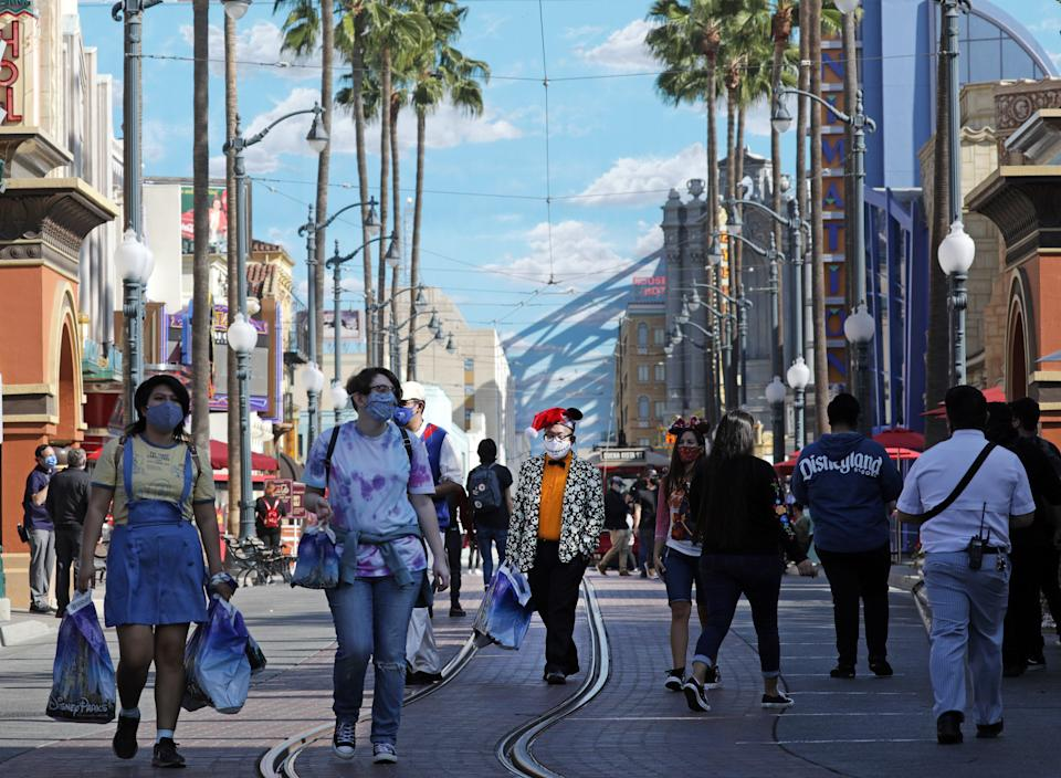 ANAHEIM, CA - NOVEMBER 19: Masked visitors walk along Hollywood Land at Disney California Adventure which opened on Thursday, Nov. 19, 2020 in Anaheim, CA but without rides. There were plenty of dining and shopping opportunities. (Myung J. Chun / Los Angeles Times via Getty Images)
