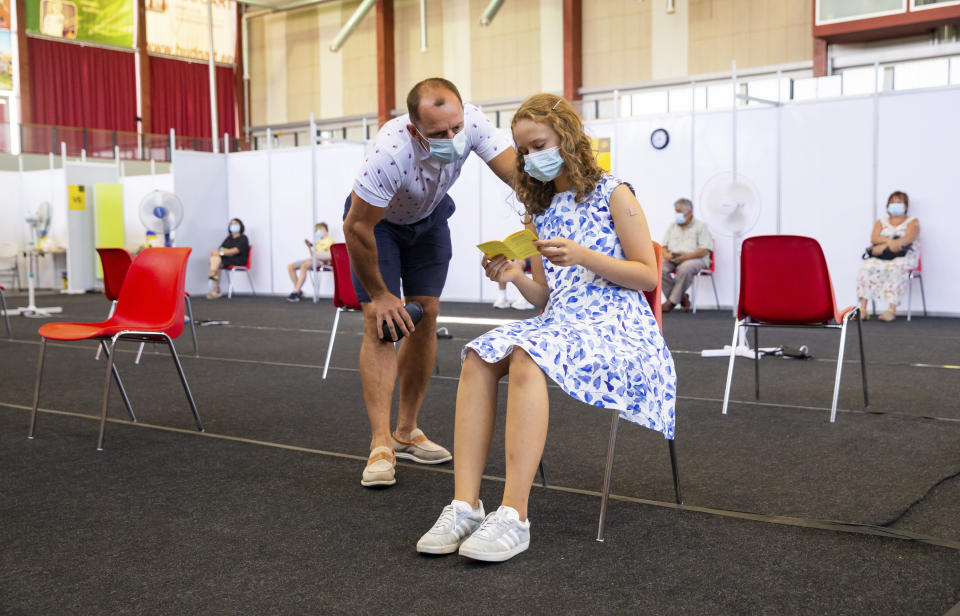 Gloria Raudjarv, 13-year-old girl, reads her vaccination certificate after getting an injection as her father Ivo, speaks to her at a vaccination center inside a sports hall in Estonia's second largest city, Tartu, 164 km. south-east from Tallinn, Estonia, Thursday, July 29, 2021. Estonia's second largest city Tartu is making rapid progress in vaccinating children aged 12-17 ahead of the school year in September. Around half of the town's teenagers have already received their first vaccine, and local health officials are confident they will hit 70% in the coming 30 days. (AP Photo/Raul Mee)