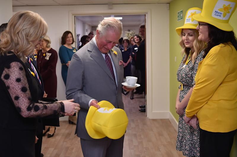 The Prince of Wales is presented with a Marie Curie yellow hat by community fundraiser Hannah Leckie and Hilary James (right) during a visit to the Marie Curie Hospice in Cardiff and the Vale, Wales.